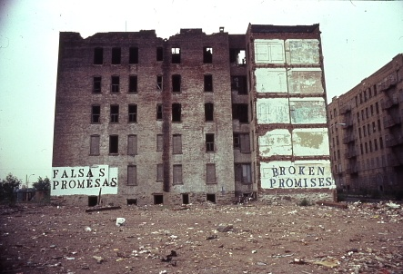 "A run down building in the Bronx, whose wall says ""Broken Promises"" in both English and Spanish"